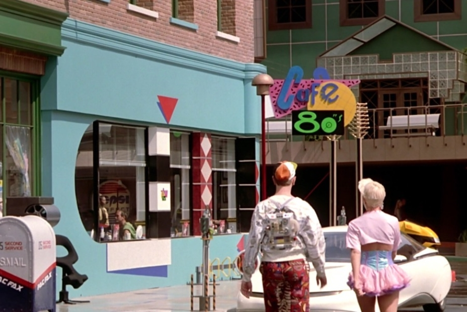 <p><strong>Figure 1.1</strong> After Marty survives the holographic shark attack, he spots the Cafe 80s, where Doc has sent him on a mission. The logo is displayed large on exterior signage, mounted on the front corner of the cafe.</p>