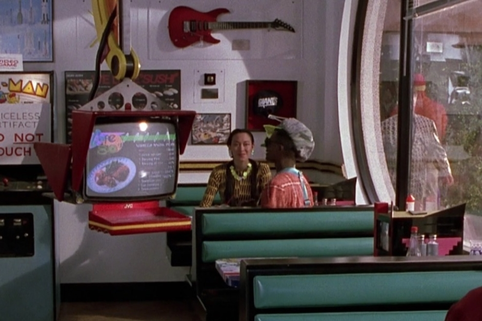 <p><strong>Figure 1.2</strong> Once inside, he is confronted with a strange scene — a mix of 1980s nostalgia and futuristic technology. A prime example is the robotic waitstaff he encounters, which feature the logo on their menu screens.</p>