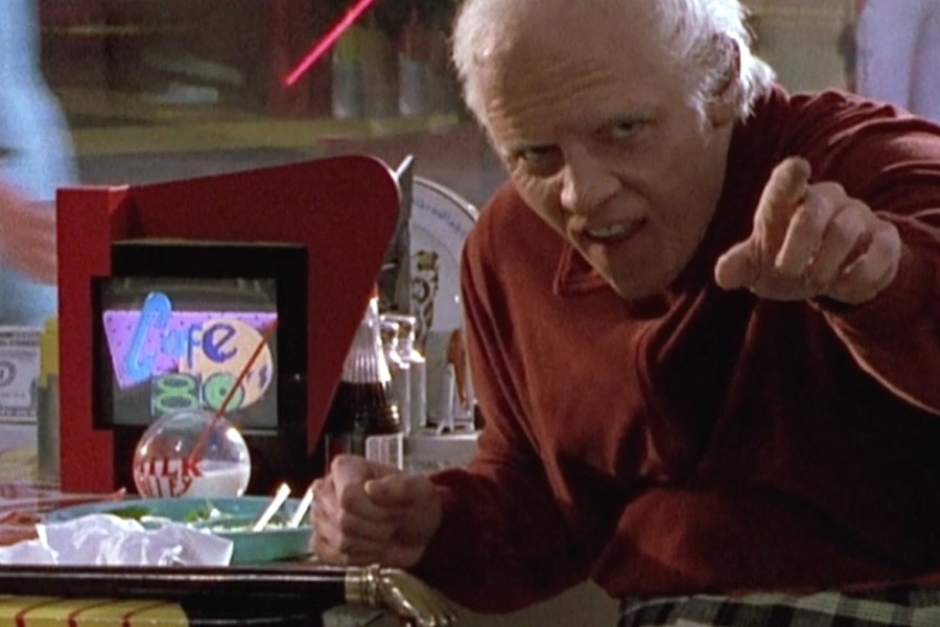 <p><strong>Figure 1.3</strong> When old 2015 Biff calls Marty out, we see the Cafe 80s logo displayed on a small retro-styled tabletop TV. Interesting that a TV replaces what would have been a little jukebox in a 50s diner.</p>