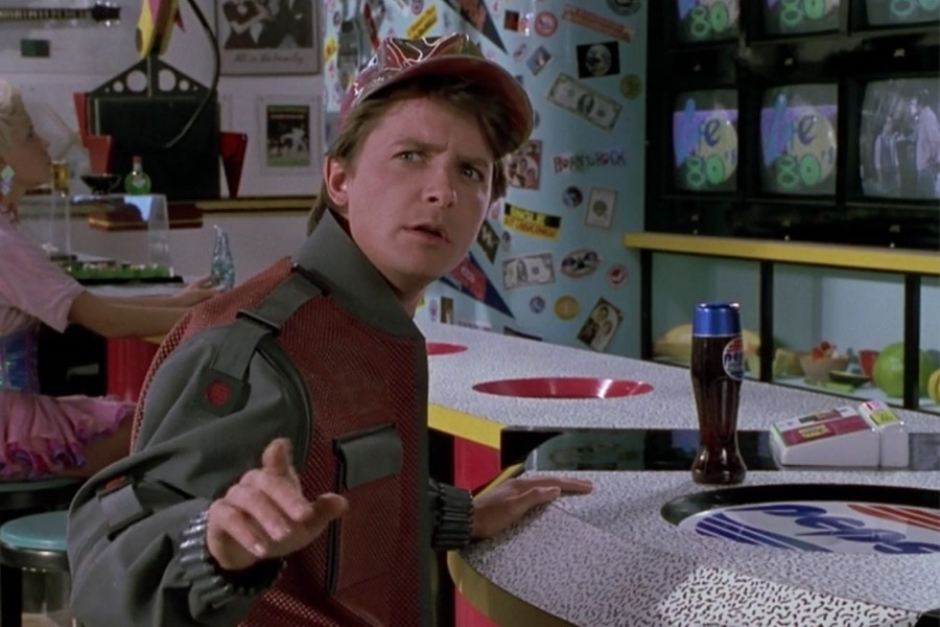 <p><strong>Figure 1.4</strong> As Marty makes the connection between old Biff and Griff, we see the Cafe 80s logo on video screens in the background. The logo pops in like a commercial between 80s TV show segments.</p>