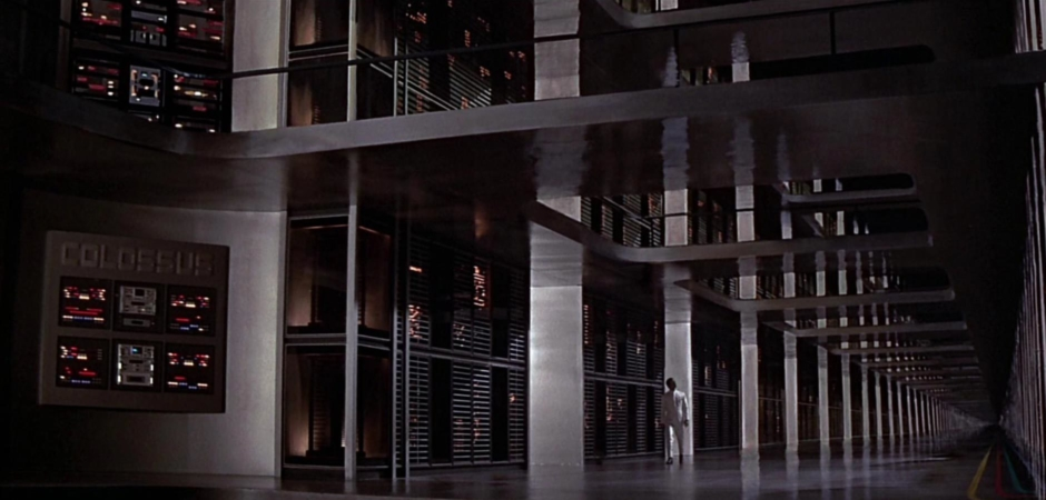 <p><strong>Figure 1.1</strong> The film opens with Dr. Charles Forbin walking the halls of a massive supercomputer complex, activating an artificial intelligence that will control the entirety of America's nuclear defense from that point forward. On the far left, a logotype is rendered large across the top of a wall-mounted bank of control panels—it reads COLOSSUS.</p>