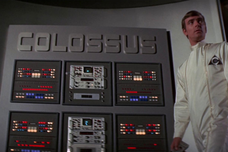 <p><strong>Figure 2.1</strong> When Forbin pauses at a large control panel to make adjustments, we glimpse the triangular logo on his white cleansuit, and in the background, the logotype for Colossus.</p>