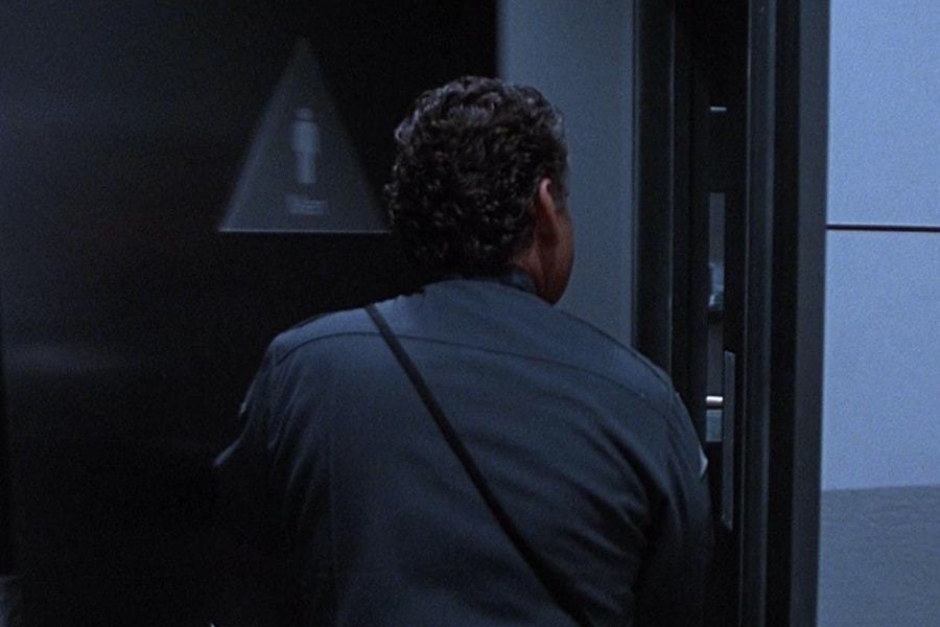 <p><strong>Figure 5.5</strong> In several shots, we can see the building's restroom door signage, which is triangular to match the Cyberdyne mark.</p>