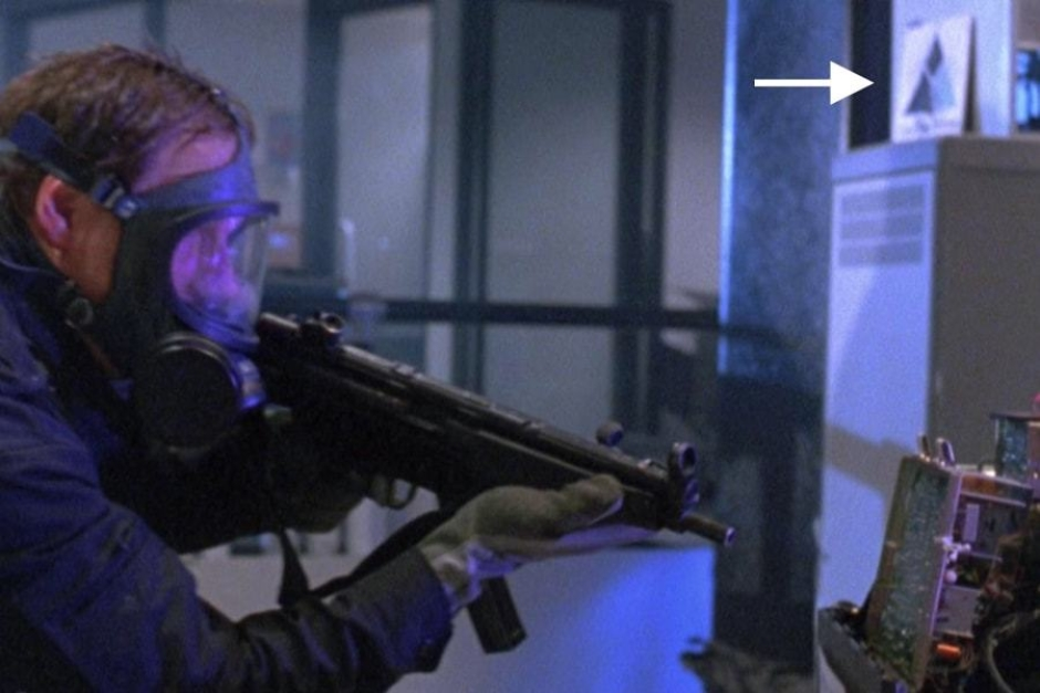 <p><strong>Figure 7.6</strong> As the SWAT team enters the lab, we can see the primary signature on a card, leaning against some electronic equipment in the background of the shot.</p>