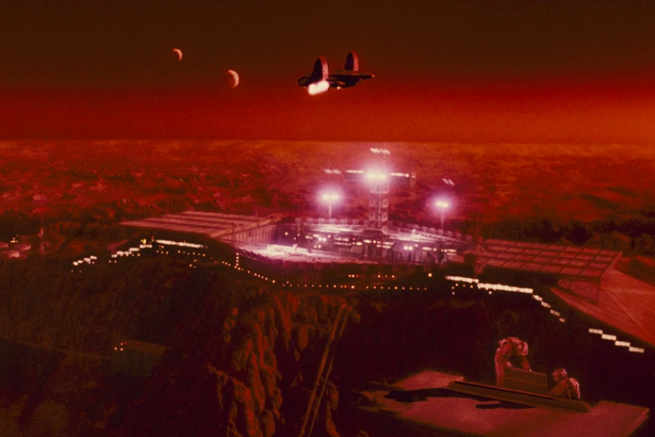 <p>A shuttle approaches the Mars colony, with its two moons in the sky overhead. The moons are featured prominently in the Federal Colonies logo. And with the Red Planet living up to its name, it's also easy to see why red hues were used in all variations of this identity.</p>