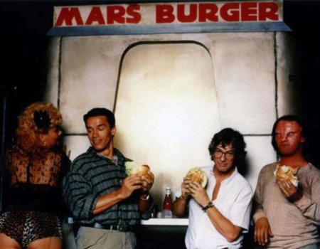 <p>Figure 1.2 The Mars Burger was used in behind the scenes photography, featuring actor Arnold Schwarzenegger (center-left) and director Paul Verhoeven (center-right). Source: <em>ScreenCrush News</em></p>