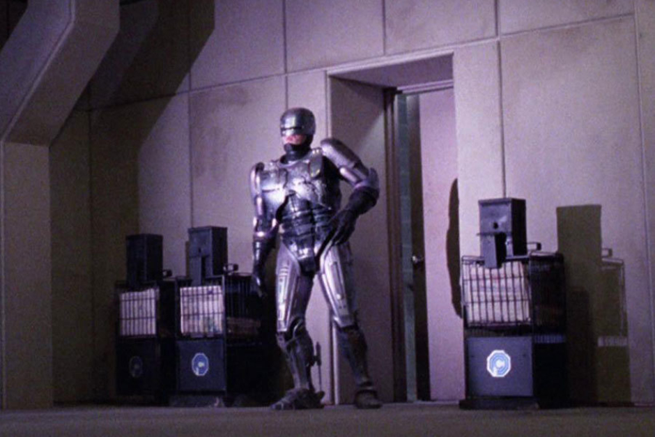 <p><strong>Figure 3.13</strong> As RoboCop exits the OCP corporate headquarters at the parking garage level, we see newspaper machines bearing the OCP mark.</p>