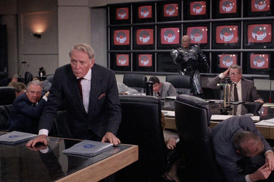 <p><strong>Figure 3.17</strong> The boardroom at OCP features a wall of television screens, which regularly display a beveled chrome OCP logo over a red background.</p>
