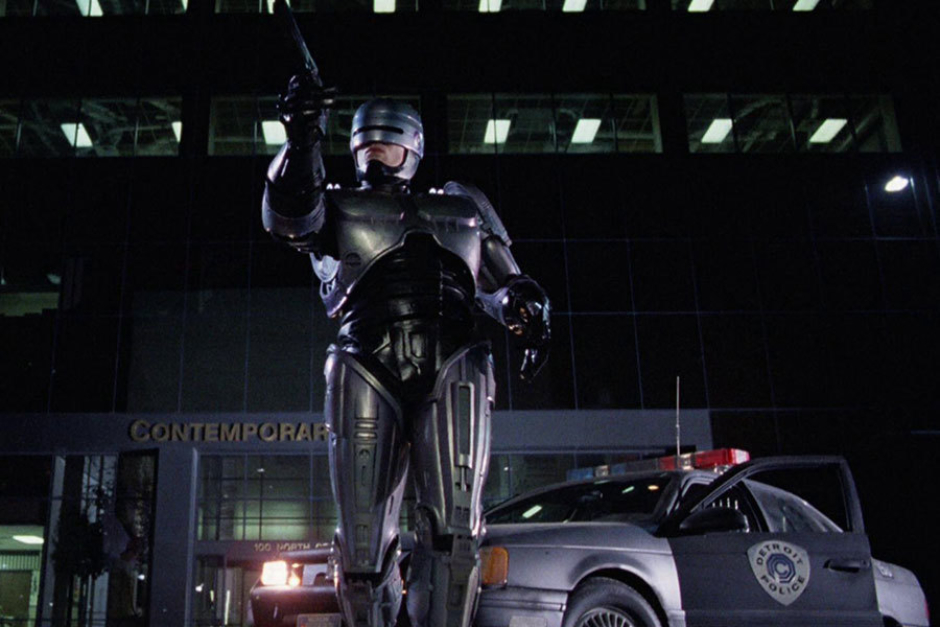 <p><strong>Figure 5.3</strong> RoboCop making an arrest, with the OCP Detroit Police shield in the background.</p>